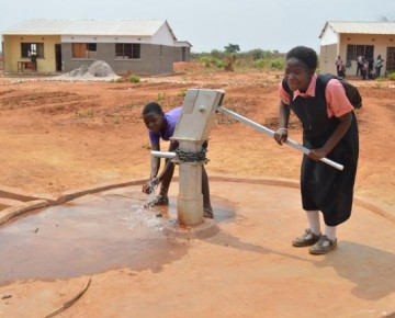 Pupils using the newly insatalled hand pump. Teachers residence in the back ground