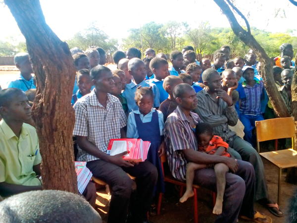 Parents, teachers, and pupils look on as fellow pupils receive educational and sports items for the school
